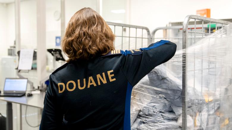 Controle pakketje door douanier in postsorteercentrum